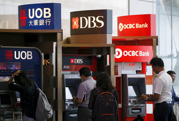 People use automated teller machines of United Overseas Bank Limited (UOB), DBS, and Oversea-Chinese Banking Corporation (OCBC) banks in Singapore January 5, 2016. REUTERS/Edgar Su - RTS878Z